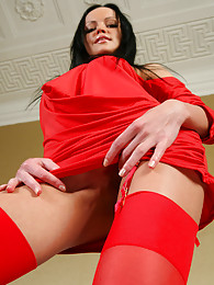 Slim brunette in a sultry red dress and matching bright red gartered nylons pictures